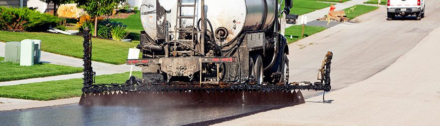 Truck applying seal coating for chip sealing asphalt pavement